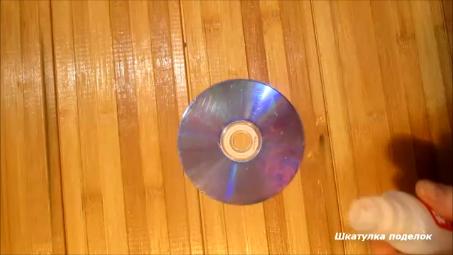 Взяла DVD диск и остатки разных страз и сделала оригинальный подсвечник.